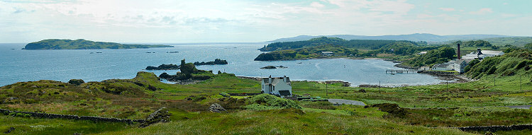 Picture of a panoramic view over a bay with the ruins of a castle and a whisky distillery (Lagavulin)